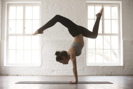 Young attractive woman in Adho Mukha Vrksasana pose, white studi